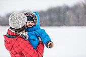 Mother and Son in Winter Forest Snowstorm
