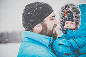 Father and Son in Winter Forest Snowstorm