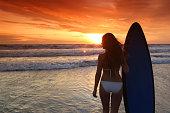 Surfer girl on beach at sunset