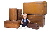 Young boy with old suitcases and boxes