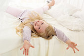 Pretty child is lying down on bed with white sheets