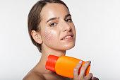 Beautiful girl with jar of sunscreen lotion