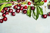 Ripe cherries on branches and leaves , top view, border.