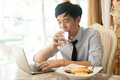 Young Asian man working while eating with his laptop