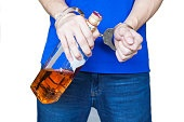 Man hand carrying alcohol drink with handcuffs