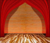 Red curtain in front of brick wall with wooden floor.