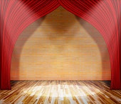 Red curtain in front of brick wall with lighting