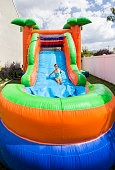 Smiling little girl playing on inflatable slide bounce house outdoors