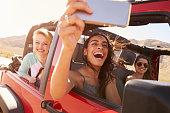 Friends On Road Trip In Convertible Car Taking Selfie
