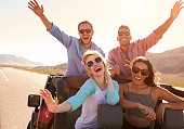 Friends On Road Trip Standing In Convertible Car