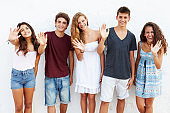 Teenage Group Leaning Against Wall Waving