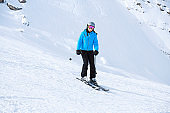 Happy Teenage girl snow skier skiing on sunny ski resorts