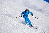 Teenage boy snow skier skiing on sunny ski resorts