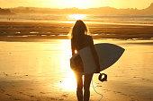 Surfer girl at sunset