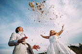bride and groom are fighting pillows outdoor