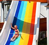 Child on water slide at aquapark hand up.