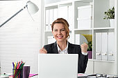 Portrait of happy businesswoman celebrating something with arms