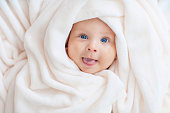 Caucasian baby boy covered with  towel joyfully smiles at camera