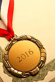 Gold Medal Inscribed With '2016' Resting On An Award Certificate