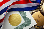 Ribbon Wrapped Around Gold Medal And Certificate