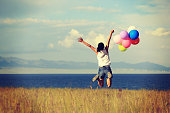 cheering young woman jumping on sunset grassland with colored balloons