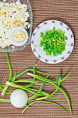 Sliced green onions and sliced eggs on plate; green onion