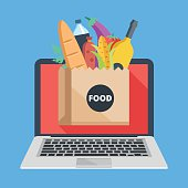 Laptop, paper bag with food. Buy groceries online, food delivery