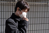 Man with a mask coughing
