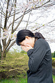 Young businesswoman crying under the cherry blossoms