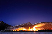 factory in front of Rocky mountains with stars at night