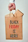 text black friday is here in a shopping bag
