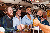 Man Group In Bar Hold Beer Glasses, Standing At Counter
