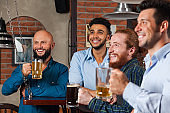 Man Group In Bar Happy Smiling And Watching Football, Drinking