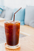 Ice coffee drink on wooden table in cafe background