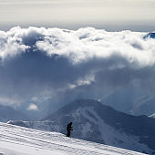 Skier downhill on snowy ski slope and sunlight storm clouds