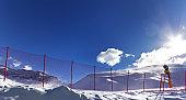 Snowy off-piste ski slope and snow gun on ski resort
