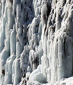 Icy mountain waterfall at cold sun day