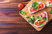 Bruschetta with ricotta, spinach, corn salad and cherry tomatoes