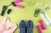 Flat lay shot of sneakers, jumping rope, water.