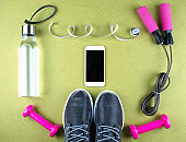 Flat lay shot of sneakers, earphones, phone.
