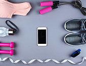 Flat lay shot of sneakers, earphones, phone.