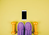 Flat lay shot of sneakers, dumbbells and smartphone on yellow background with copy space for your text.