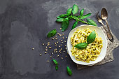 Fettuccine pasta with pesto sauce, basil and pine nuts on concrete background