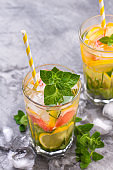 Cold refreshing summer lemonade in a glass on a grey concrete or stone background.