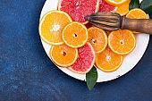 Fresh oranges, grapefruits and madarine slices on dark stone background.