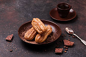 Chocolate eclair and coffee cup on dark background