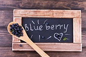 Blueberries in a wooden spoon on a vintage wooden table with black chalkboard. Healthy food concept.