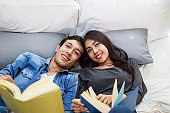Young Asian couple lying on the bed reading book at home, Love relationship concept