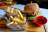 Cheese hamburger with fries and ketchup on wooden board