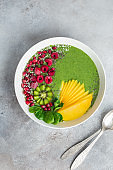 fresh green smoothie bowl with spinach, mango, kiwi and raspberry. Healthy vegan raw food
